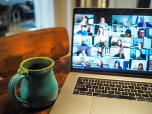 Mug to the left of a laptop with people on a virtual platform.